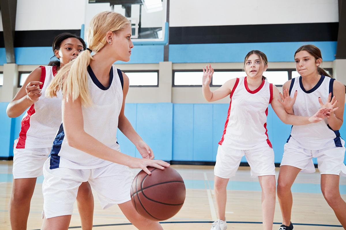 female-high-school-basketball-team-dribbling-ball-QMENWP7