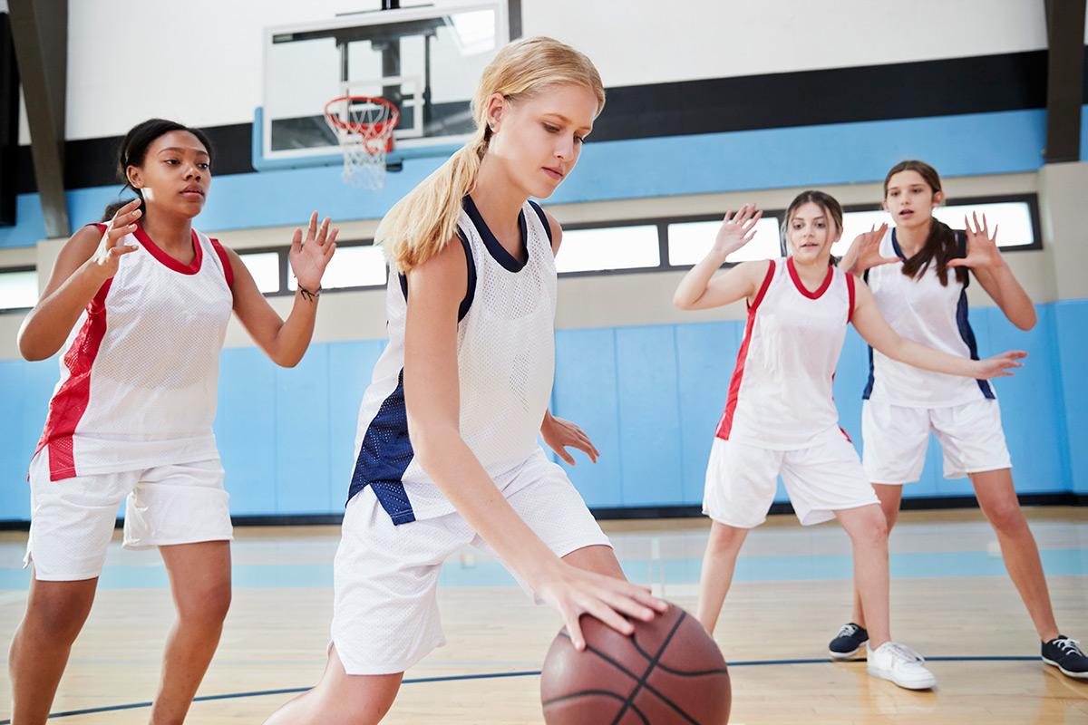 female-high-school-basketball-team-dribbling-ball-WXMFANY