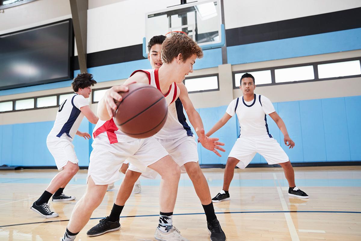 male-high-school-basketball-team-dribbling-ball-BFVWXL6